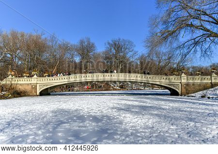 New York City - Feb 21, 2021: Snow Covered Frozen Lake Around The Bow Bridge With Tourists In Centra