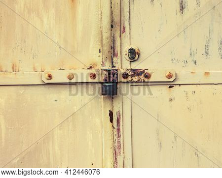 Rusty Metal Latch With Lock Housing Of Cargo Garage Or Warehouse. Corrosion Stains On Metal Sheet Ga