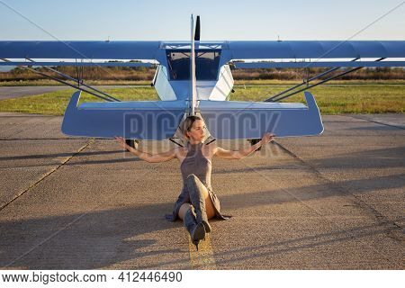 Beautiful Woman In Gray Dress Sitting In Front Of Private Plane. Blue Aircraft On Aerodrome. Pretty