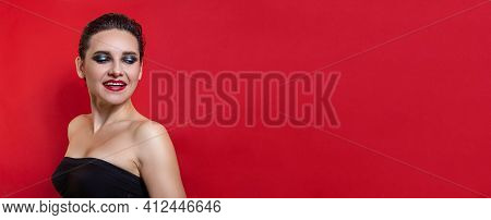 Horizontal Banner. Arrogant Pretty Woman With Bright Makeup Posing On Red Studio Background. Copy Sp