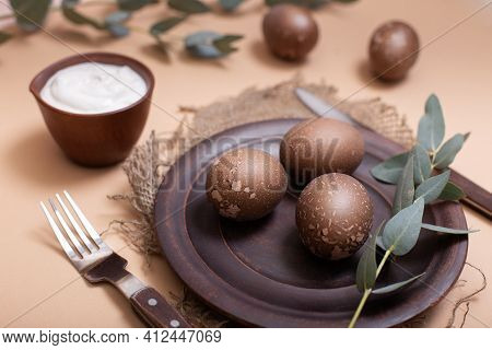 Ceramic Brown Plate On Sustainable Burlap Cloth With Easter Eggs, Bowl, White Cream Sauce And Eucaly