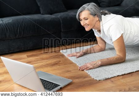Close-up Portrait Of Senior Woman In Plank Position Watching Sports Video Tutorial On The Laptop Com