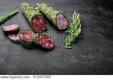 Fuet Salami Sausage In Herbs On Black Background With Copy Space.