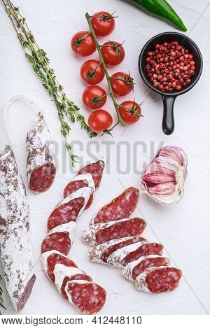 Dry Cured Fuet Salami Sausage Slices With Herbs On White Surface, Top View.