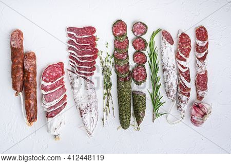 Variety Of Dry Cured Fuet And Chorizosalami Sausages, Whole And Sliced On White Surface, Flat Lay.