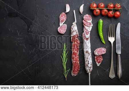 Dry Cured Fuet Salami Sausage Slices  On Balck Background, Flat Lay With Copy Space.