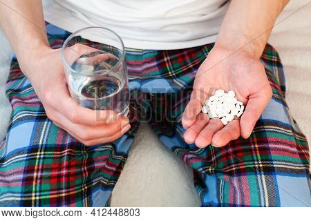 Young Man Holds Handful White Pills And Glass Of Water In Hands. Taking Vitamins, Supplements, Antib