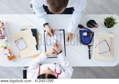 Doctor Passes Business Card To Patient At Work Table