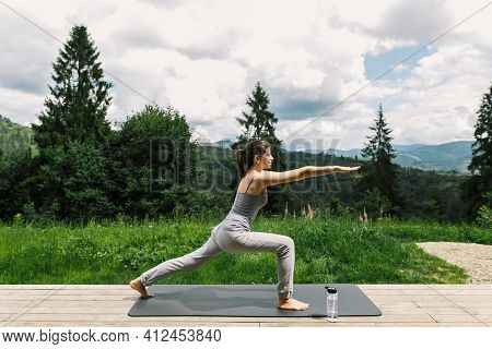 Young Fit Woman Stretching Or Doing Squats On Yoga Mat At Sunny Mountains. Outdoor Workout, Training