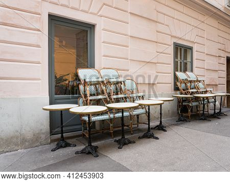 Chairs And Stools Stacked On Tables In Front Of An Empty Closed Restaurant Cafe During Covid-19 Coro