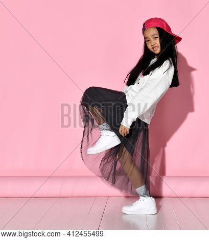 Side View Of Fashion Portrait Of Little Korean Girl Model Posing In Studio Against Pink Background L