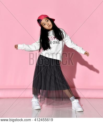 Cool Asian Little Girl Standing With Her Arms Outstretched Against A Pink Wall Background. The Child