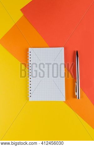 Yellow And Orange Office Desk Table With Blank Notebook And Other Office Supplies. Top View With Cop