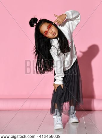 Fashionable Portrait Of A Little Korean Model Girl Who Is Professionally Posing On A Pink Background