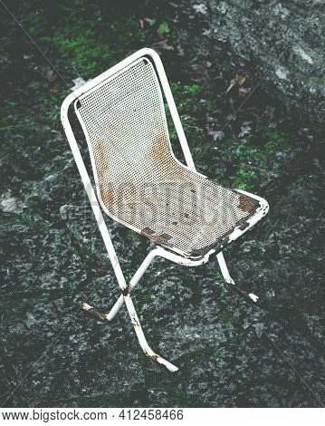 Old, Rusty Metal Chair On Stone Background. Scenic, White, Abandoned Outdoor Beach Cafe Furniture. D