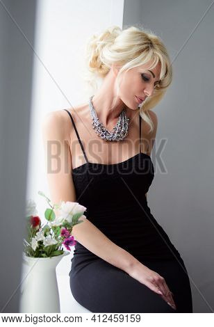 Adult Blonde Natural Beauty Woman With Hairdo And Necklace In Elegant Black Dress. Femininity Concep