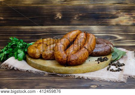A Set Of Traditional Homemade Smoked And Raw Sausages On A Round Wooden Board. Dark Wooden Rustic Ba