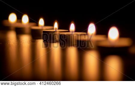 Closeup Of Many Candles Burning. The Candle Light Is Reflected