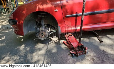 Car Service Process Of Breaking Wheel Repair. Jack Tool Near Red Car Without Wheel While Maintenance