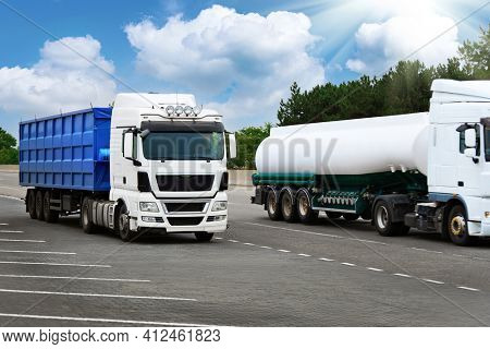 trucks is on a road - cargo transportation, shipping concept, blue container and white tanker truck, blank space on a side view