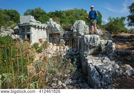Hiking Lycian way. Man is standing on ruins of ancient city of Phellos on Lycian way trail, Trekking in Turkey, outdoor activity in sunny day