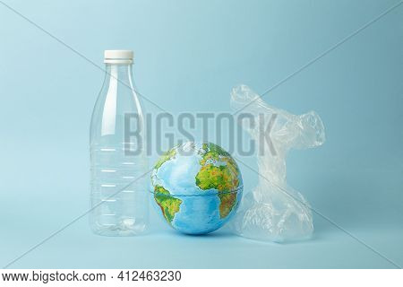 Plastic Bag Pollution Concept. Earth Globe In A Plastic Bag On A Colored Background. Plastic And Was