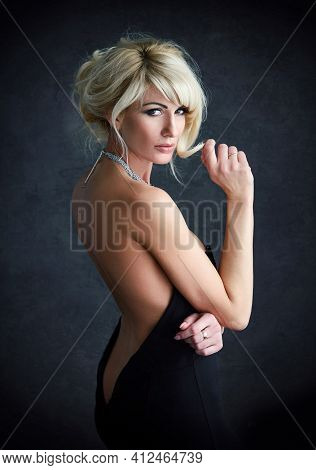 Adult Blonde Woman With Hairdo In Elegant Black Dress With An Open Back. Femininity Concept