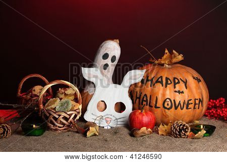 Trick or treat halloween masks and  buckets filled with cookies on color background