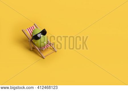 Minimal  Funny Composition With Easter Egg With Sunglasses While Sitting On Deck Chair On Illuminati