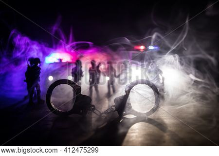 Police Raid At Night And You Are Under Arrest Concept. Silhouette Of Handcuffs With Police Car On Ba