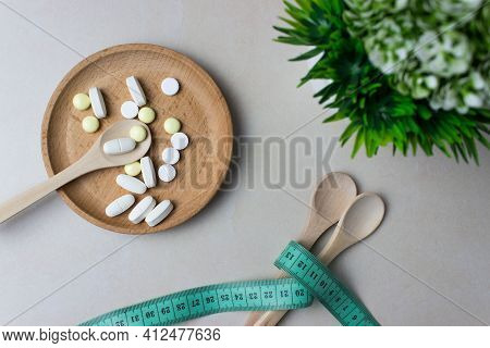 A Handful Of Pills In A Wooden Plate With Spoon And Green Plant. Near Are Two Wooden Spoons Tied Wit
