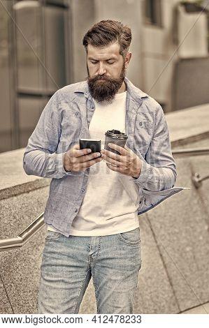 Coffee Talk During Break. Bearded Man Hold Takeaway Cup And Smartphone. Enjoying Coffee Break. Moder