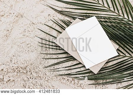 Summer Stationery Still Life. Closeup Of Blank Card Mock-up And Craft Envelope On Green Date Palm Le