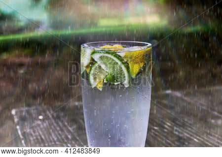 Lemonade with lemons an lime outdoor on table with artificial spring rain
