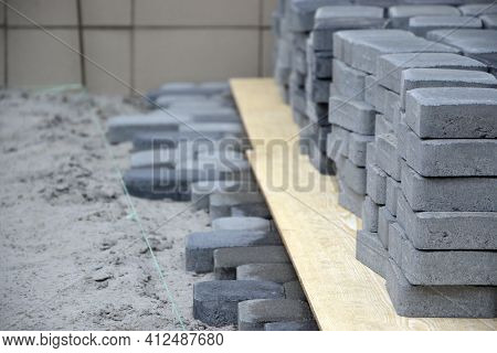 Rows Of Gray And Dark Grey Walkway Slab Lying Outdoors. Material For Paving Slabs By Mosaic In Progr