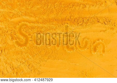 The Word Tan Is Written On The Orange Beach Sand. Sign And Symbol Of Skin Color Change.