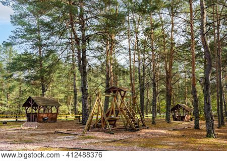 Recreation Area With A Playground In The Forest Near The Road. Autumnal Pine Forest Landscape. Conif