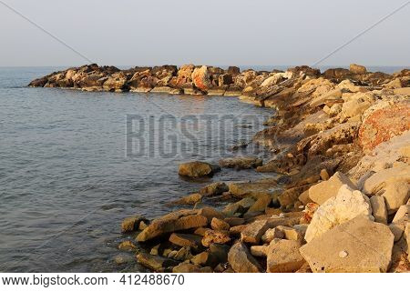 Massive Concrete Blocks And Large Stones Are Laid In A Breakwater On The Shores Of The Mediterranean