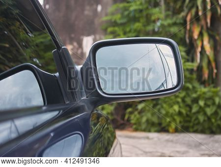 Car Wing Mirror Or Side Mirror On Green Tree Background With Natural Light