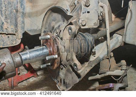 Car Mechanic Or Auto Mechanic Tighten Drive Axle Shaft Hub Nut On Wheel Hub By Wind Block And Hang B