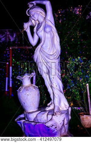 Fountain Statue Of A Young Lady Fetching Water With Small Pot And Pouring Into A Large Water Jar