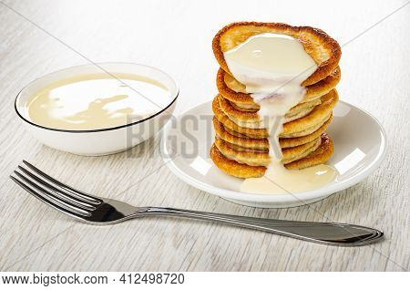 Bowl With Condensed Milk, Stack Of Small Pancakes Poured Condensed Milk In White Saucer, Fork On Woo