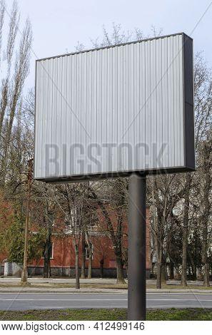 A Gray, Empty Billboard On A City Street. Rectangular Billboard Against A Background Of Spring Trees