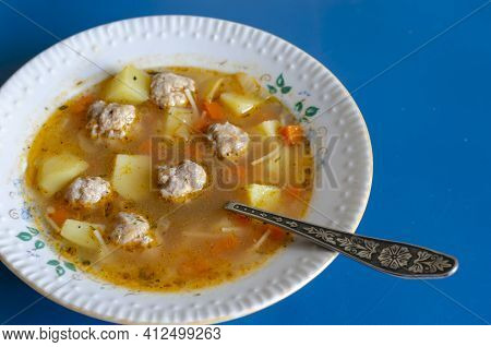 Soup With Meatballs In A White Ceramic Plate And A Metal Spoon On Blue. Portion Ready To Eat Soup. M