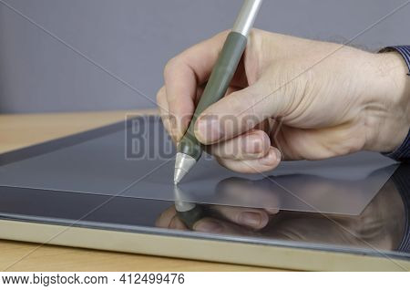 A Designer's Hand Drawing With A Special Pen On The Screen Of A Graphics Tablet. A Man's Hand And A