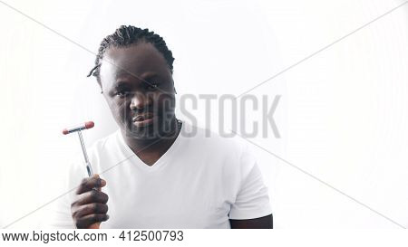 African American Black Man With Crossed Hands Over The Chest Holding Medical Reflex Hammer. Isolated
