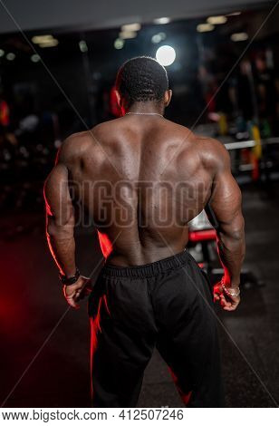 High And Shirtless Man Poses With Very Muscular Back To The Camera. African American Bodybuilder Wit