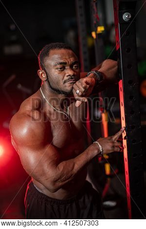 Bodybuilder Leaned At Sport Equioment And Poses Without T-shirt In Thoughtful Mood. Handsome And Mus