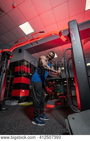 Cute Young African American Poses To The Camera While Training In Gym On Sport Equimpent. Full Body
