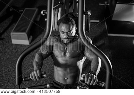 Strong And Muscular Man Trains On Modern Equipment In Gym. Black And White Portrait Of Muscular Pump